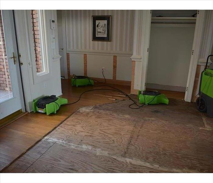 cut and removed wood floorboards, showing sheathing subfloor and drying equipment