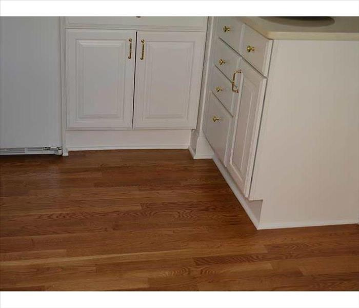 newly installed hardwood flooring, abutted to the white kitchen base cabinets